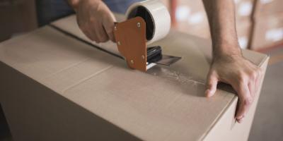 A man tapes a cardboard box shut.